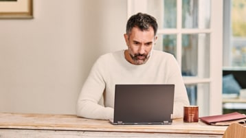 A person sitting at a table using a laptop.