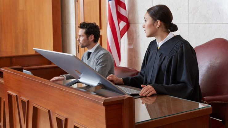 A judge and a colleague sitting at their desk in front of a large computer.
