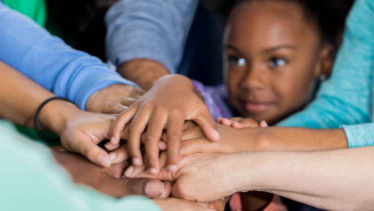 Children and adults stacking hands.