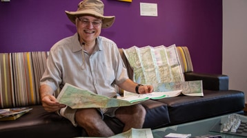 Apple smiles as he reads an unfolded traditional map. He's wearing an explorer's hat and shorts and a short-sleeved shirt.