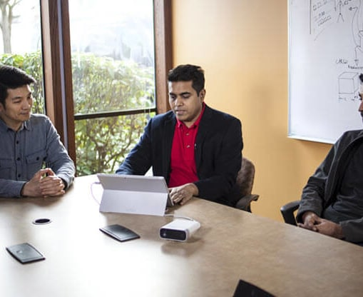 Three men sitting in an office looking at a computer.
