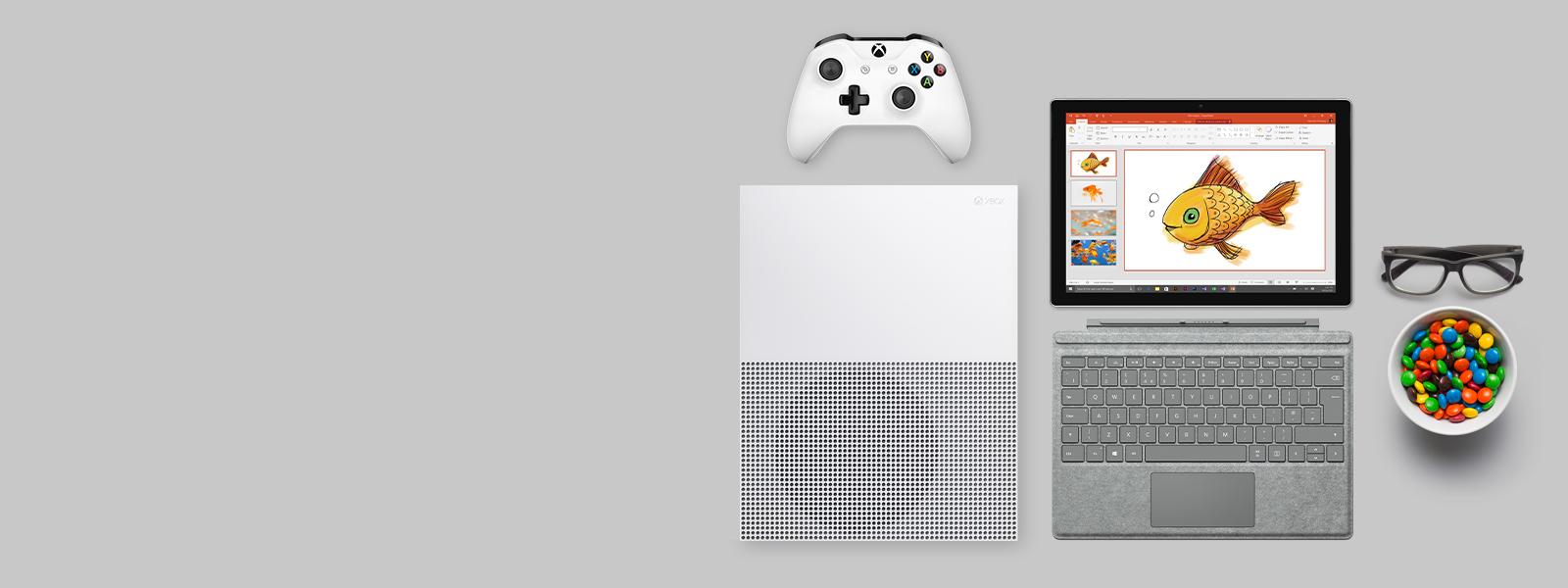 Eine Xbox One S mit Wireless Controller und ein Surface Pro mit Signature Type Cover zusammen mit einer Schale mit Schokolinsen und einer Brille abgebildet