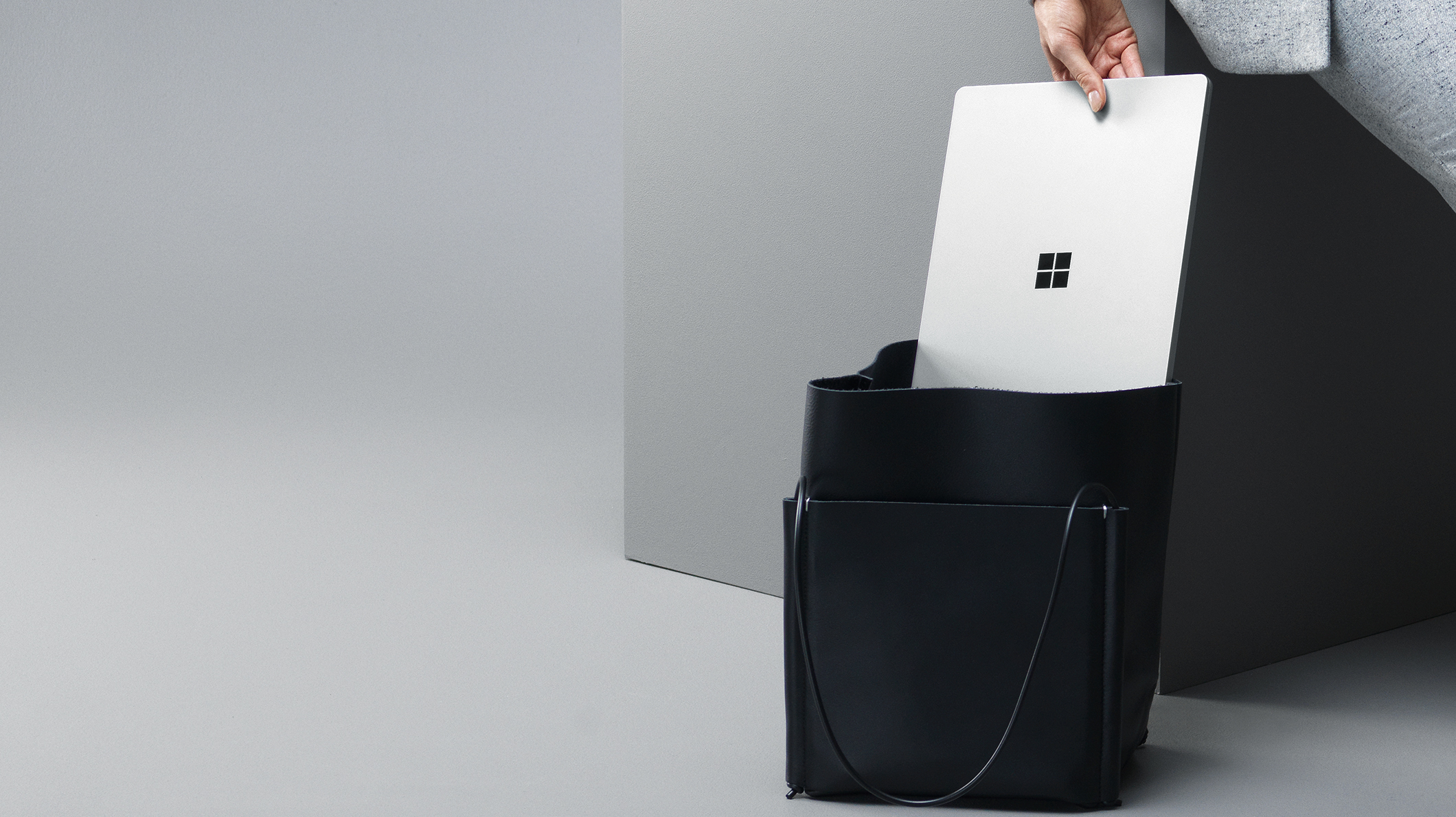 A woman places a Surface Laptop in a bag