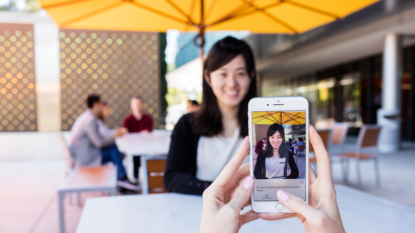 A smart phone with Seeing AI app running and pointing towards a person at a restaurant. The app suggests she is a 25 year old woman with black hair looking happy. Credit: Tyler Mussetter