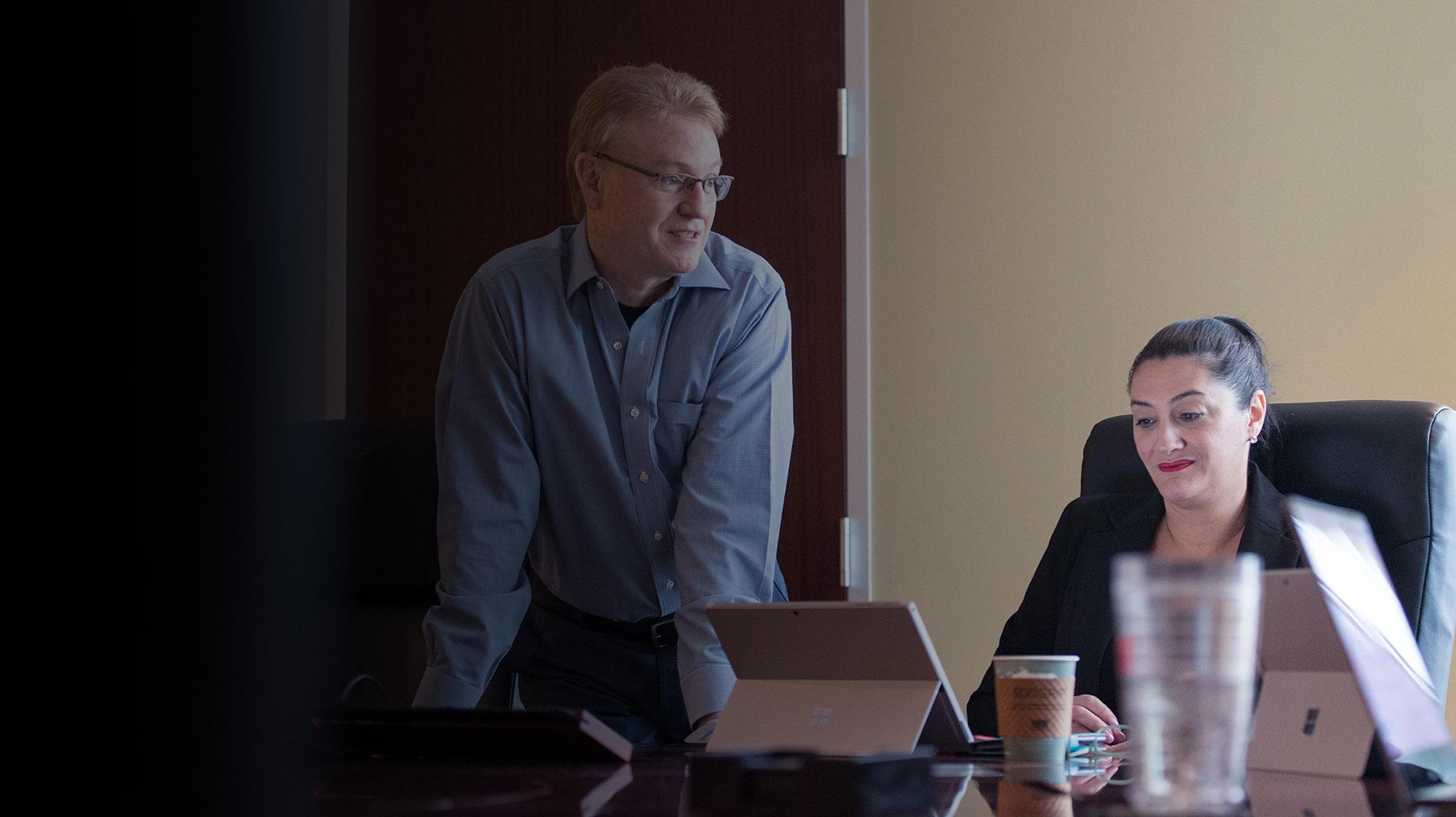 Ein Mann steht neben einer Frau, die an einem Konferenztisch sitzt und auf ihr Surface Pro blickt.
