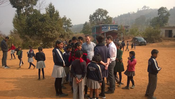 Local children gathering around visiting entrepreneurs.
