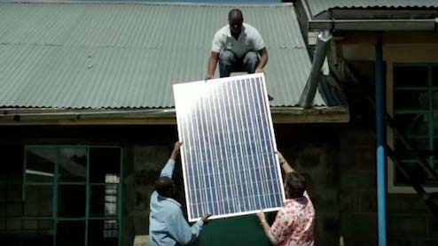 Workers installing solar panels on an African schoolhouse