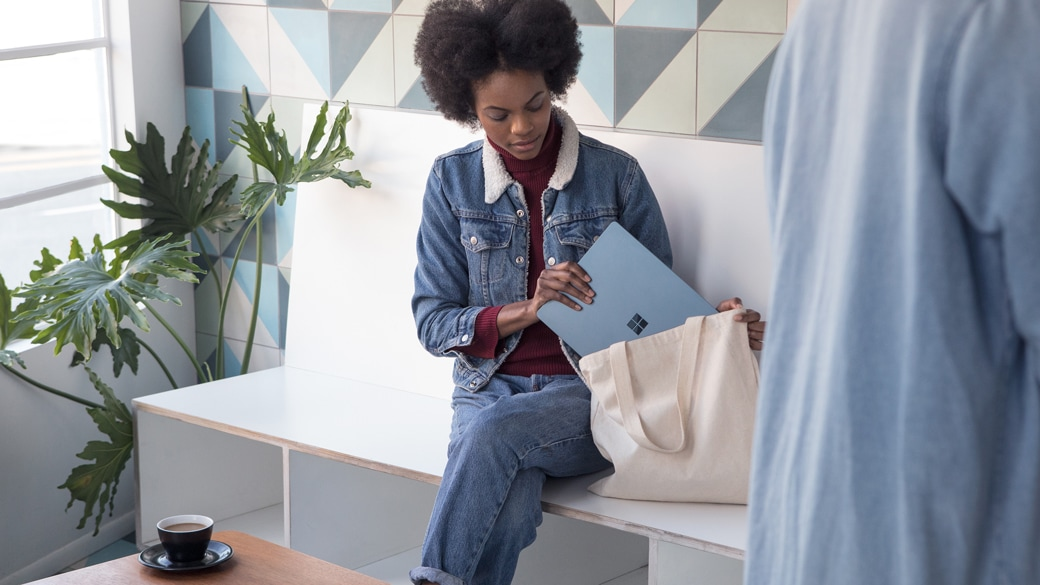 Woman putting a Surface Laptop into a tote bag