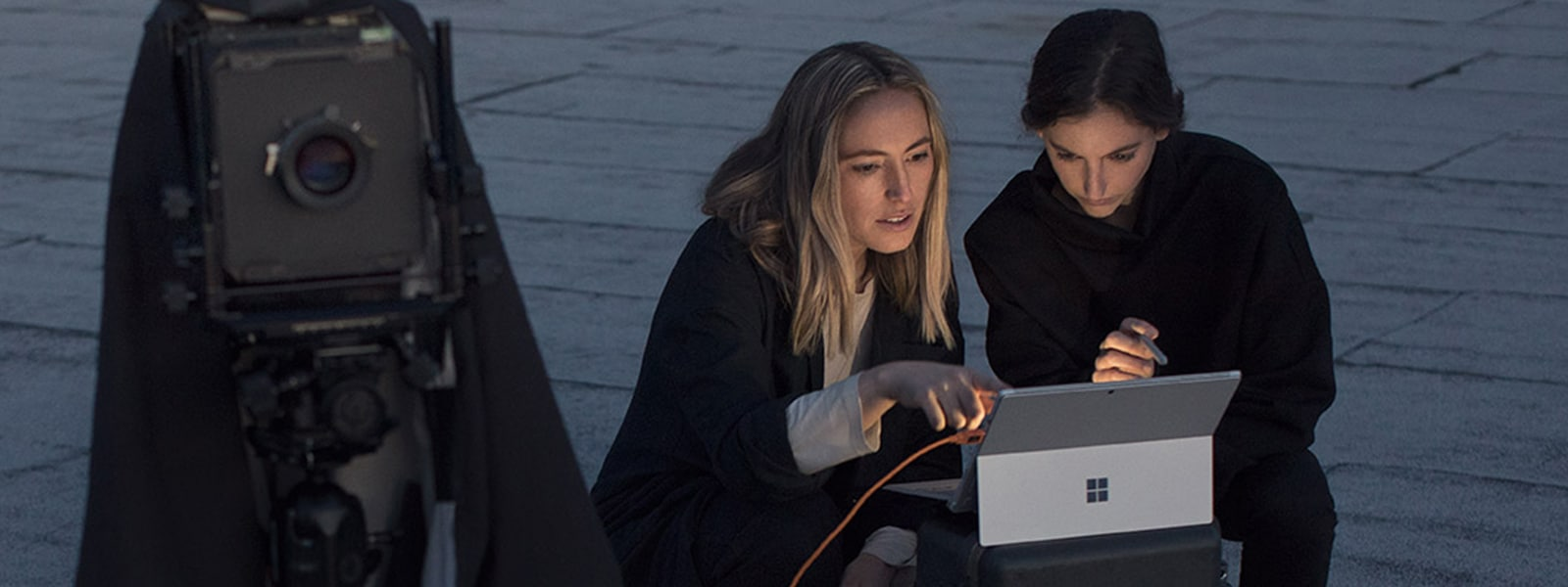 Two women shooting video and editing it on their Surface Pro