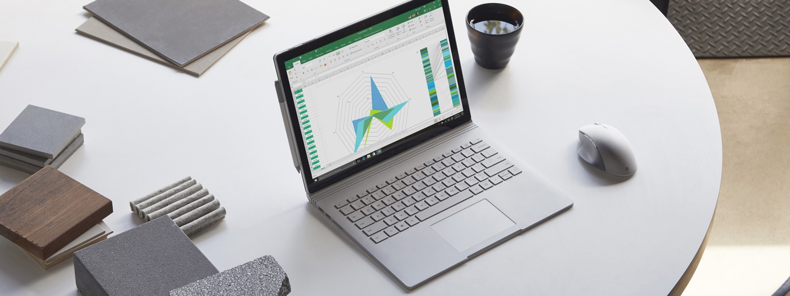 Surface Book 2 with Surface Pen attached to the side, Microsoft Surface Precision Mouse on the right, on a table.