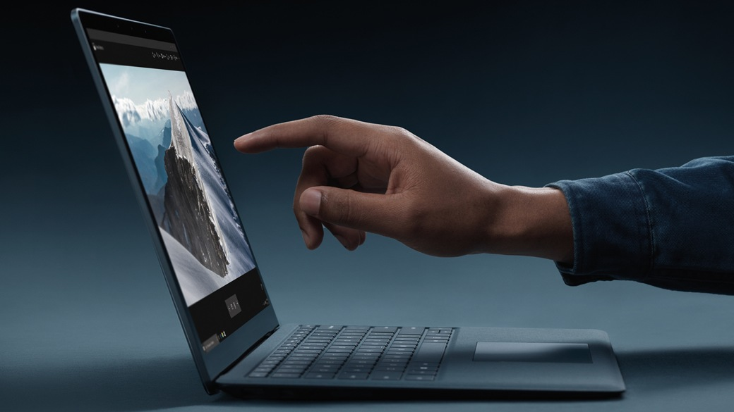 Person about to touch the touchscreen on a Surface Laptop