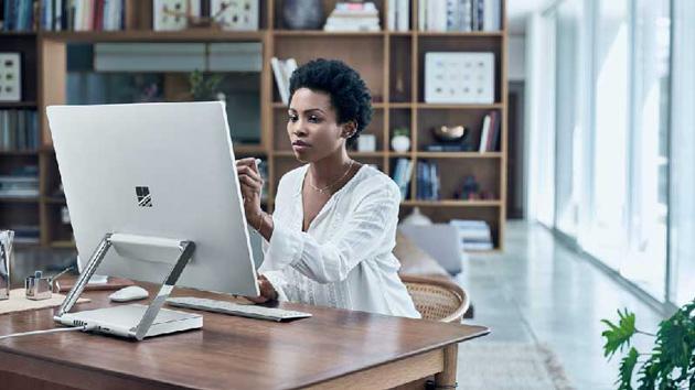 Een vrouw werkt thuis op haar desktop