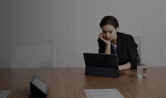 dark haired woman working in a conference room on her laptop