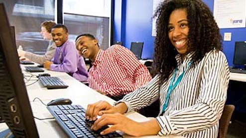 People sitting at computers laughing.