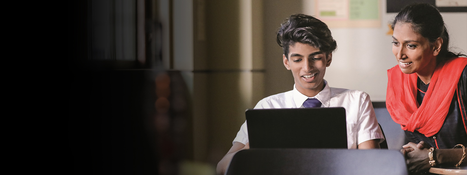 A young man works on a laptop while a woman looks over his shoulder.