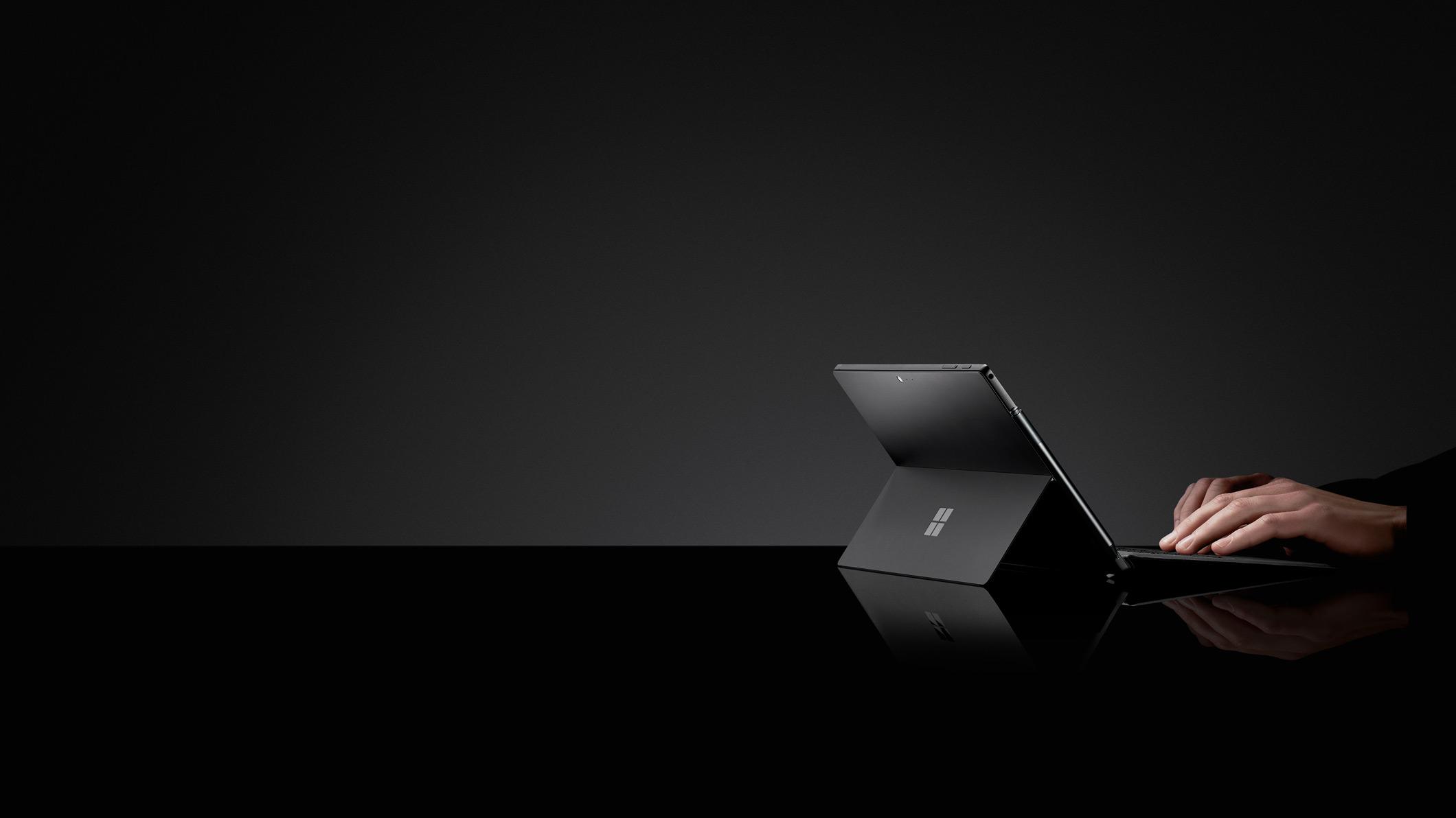 黑色背景上,一个人在用黑色 Surface Pro 6 打字