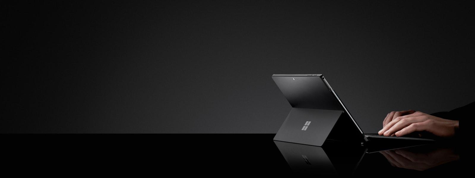 黑色背景下,一个人在典雅黑色颜色的 Surface Pro 6 上打字