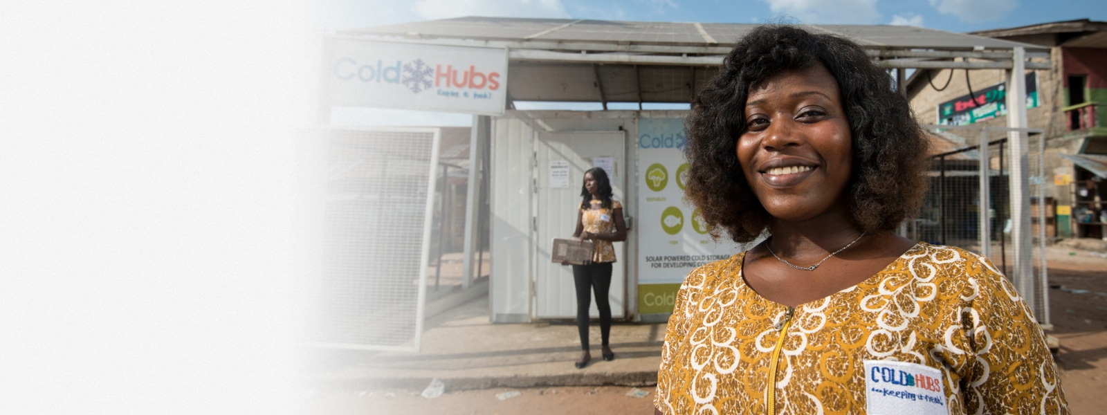 A woman from ColdHubs, one of the recipients of the Microsoft Airband Grant Fund, stands and smiles.