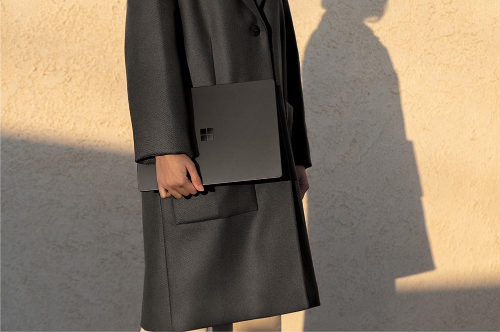 一人手里拿着典雅黑色 Surface Laptop 2