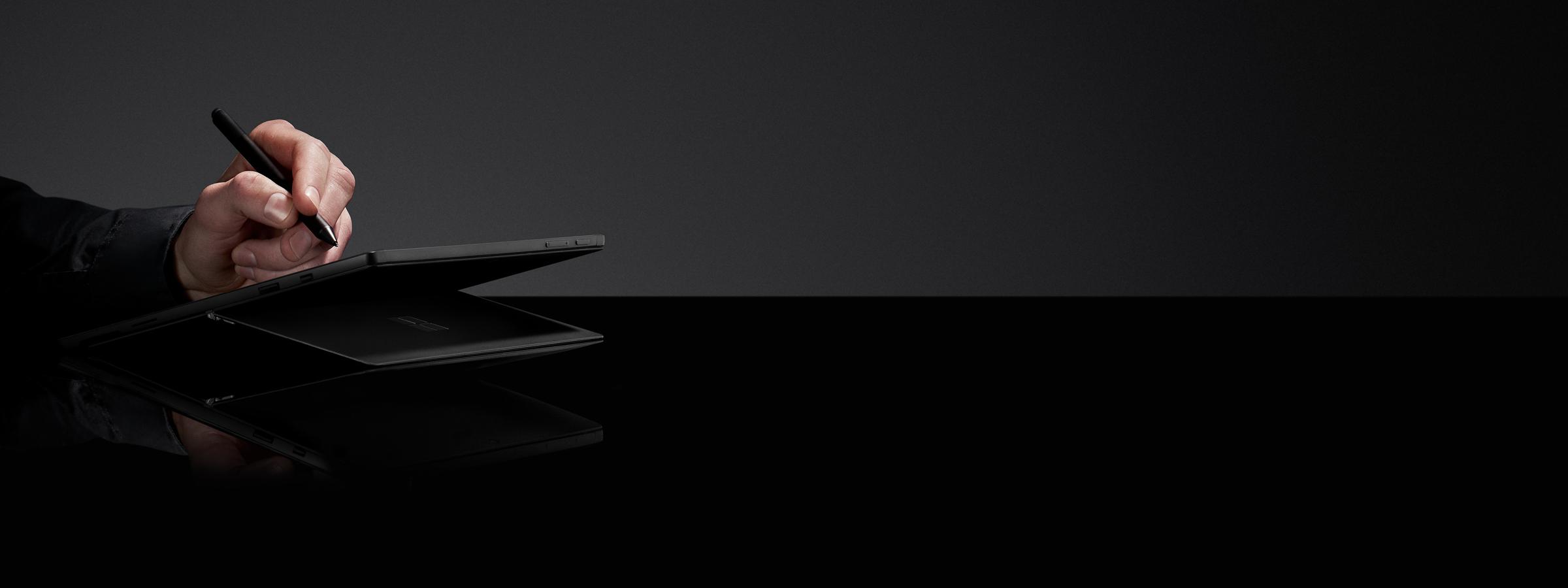 黑色背景上,一个人在黑色 Surface Pro 6 上使用 Surface 触控笔