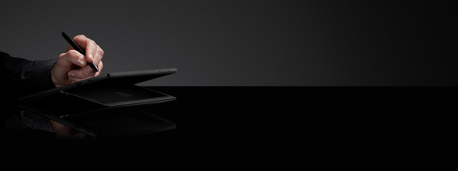 黑色背景下,一個人在典雅黑色顏色的 Surface Pro 6 上使用 Surface 觸控筆