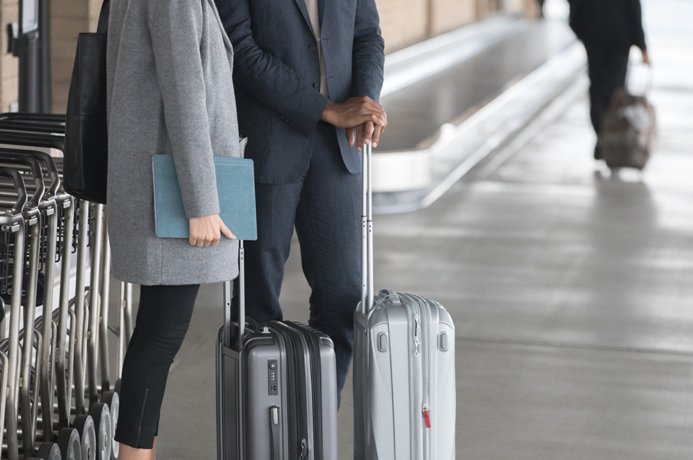 A man and woman standing with their luggage at an airport