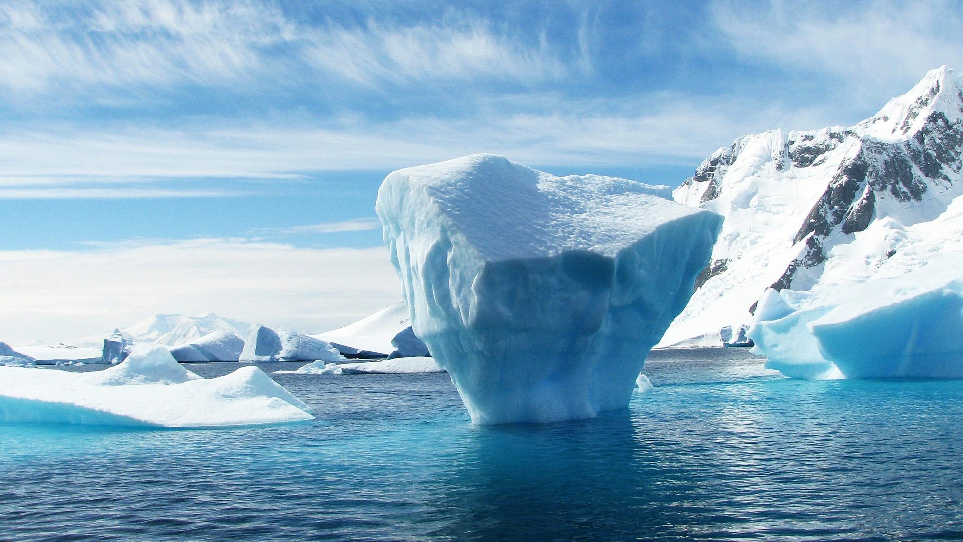 Icebergs float in artic blue water