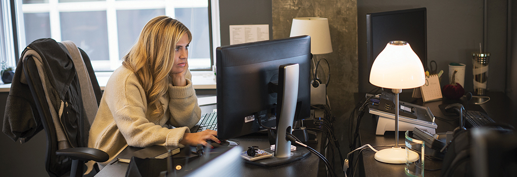 Photograph of person seated at desk in a shared office looking closely at their desktop monitor