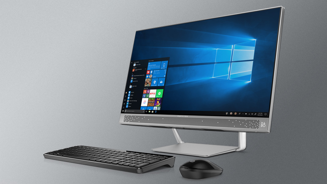 A Windows 10 All-in-One sitting on a grey background with a keyboard and mouse in front of it