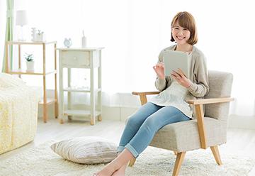 タブレットを片手に座る笑顔の女性