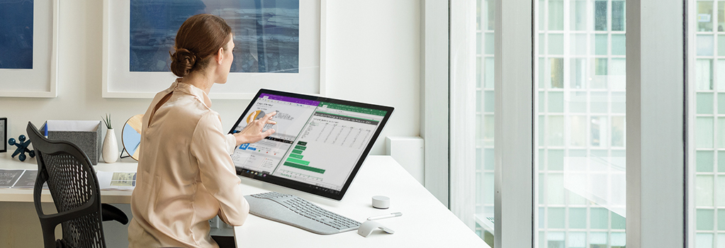 Photograph of a person at a desk in a modern office touching the screen of a Surface Studio 2 that is displaying graphic information.