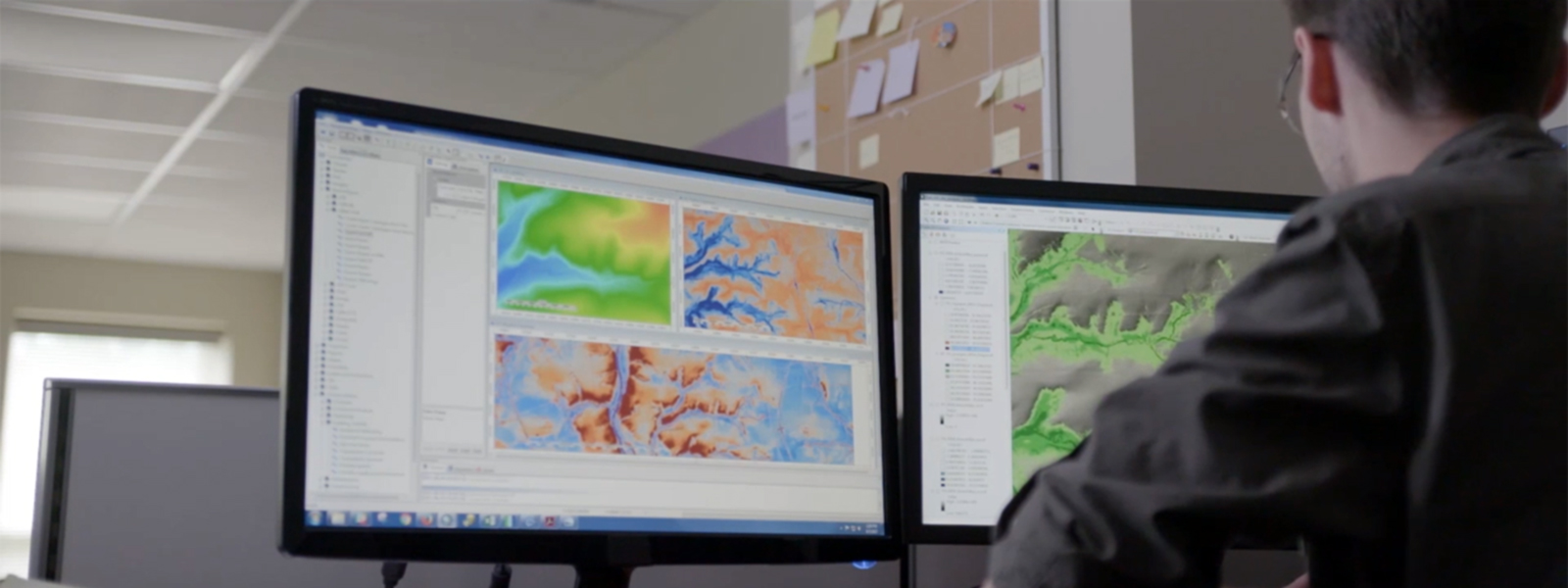 Man works on 2 monitors showing mapping application.