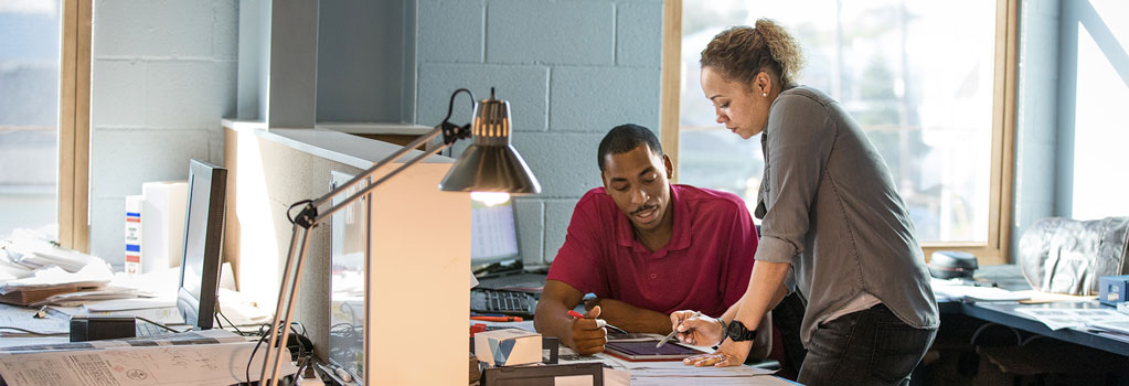 Picture of a man and a woman at a desk while using a touch-screen device and pen