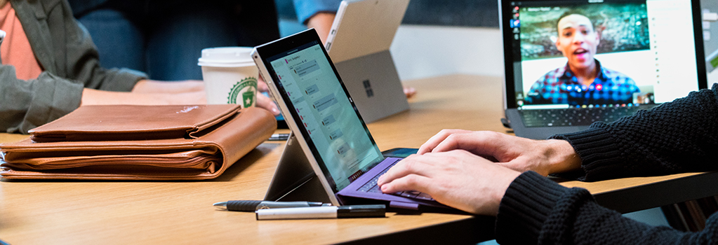 Close-up photograph of people at a conference table with multiple Surface Pros in Laptop Mode. They are participating in a multi-media conference call with video, audio, and chat.