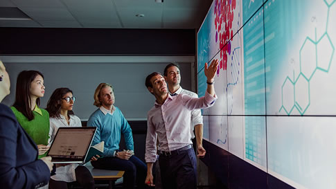 group of professionals looking at data on large display