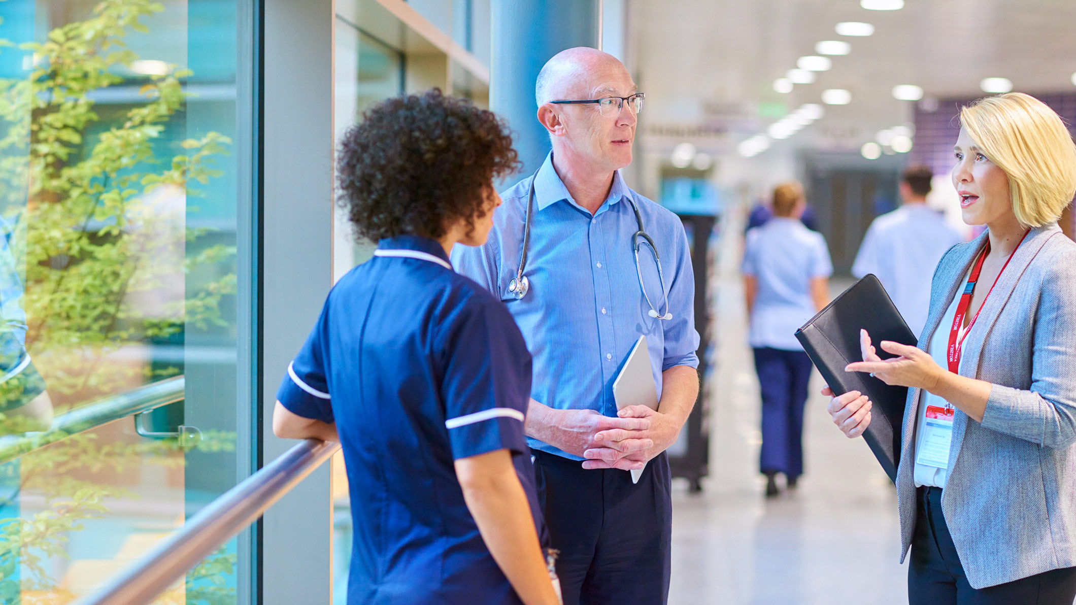 medical professionals talking in hospital corridor