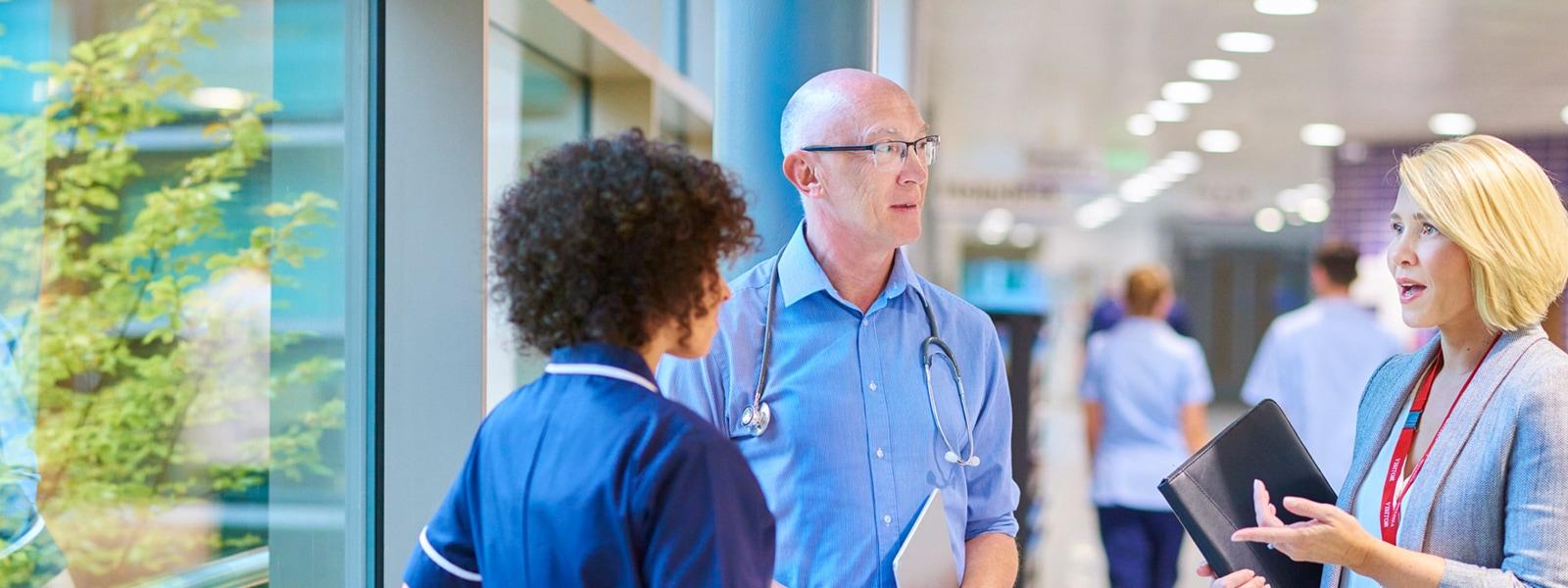 Medical professionals talking in hospital corridor
