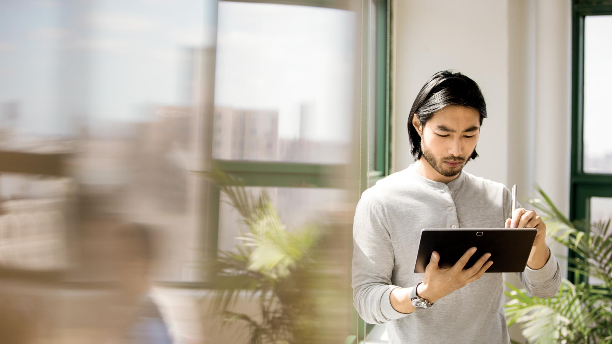 Ein Mann in einem Büro arbeitet an einem Surface Laptop.