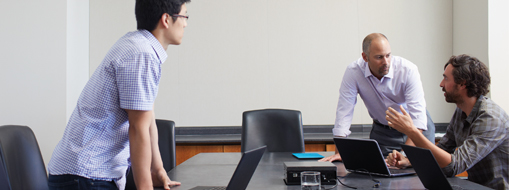Three people having a meeting in a conference room, read the case study about how Microsoft Enterprise Commerce uses Microsoft Project Online