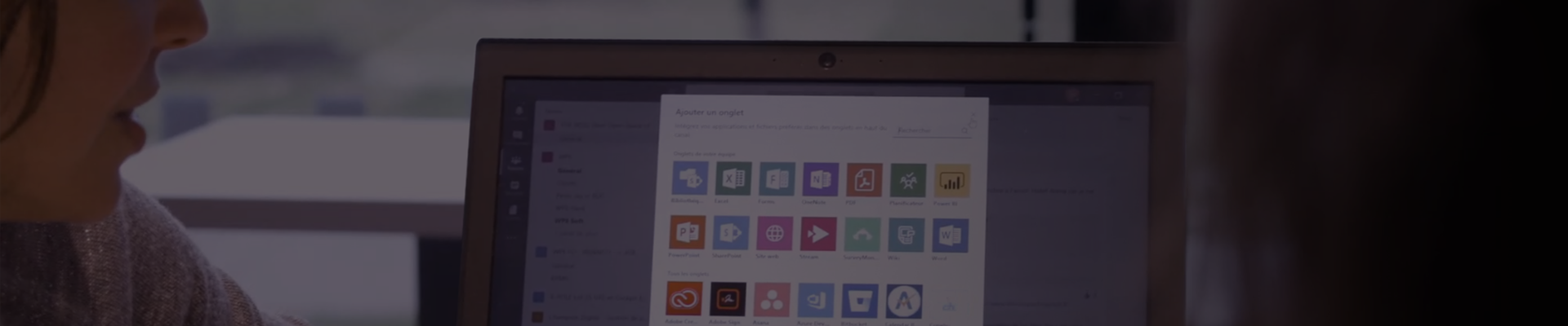 Muted still image from video about Schneider Electric and Microsoft Teams showing a person looking at a grid of app icons on a display monitor