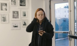 A woman working from her phone while entering a building
