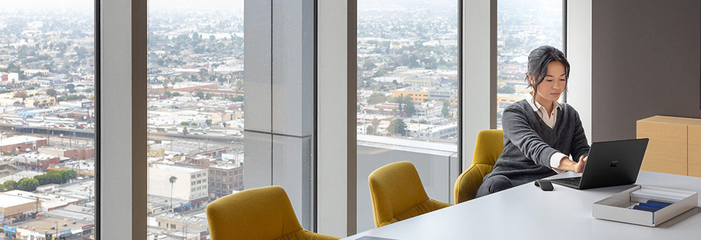 Photograph of a person seated at a conference table in a high-rise office building working on a Surface Book.