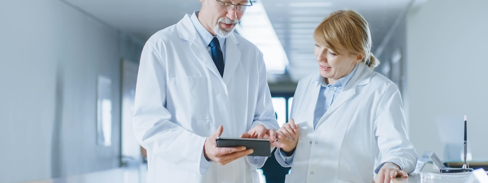 Two medical professionals looking at tablet in hospital setting