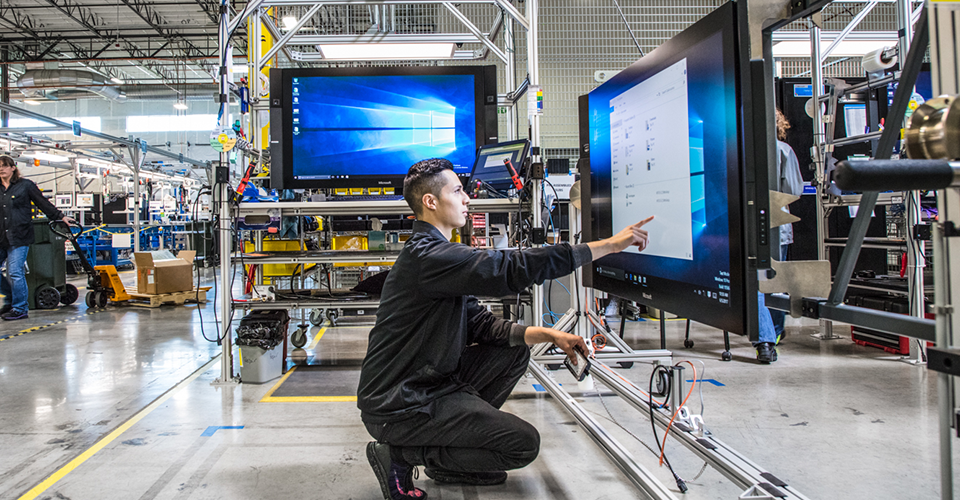 Photograph of a person in a modern factory touching the screen on a large monitor