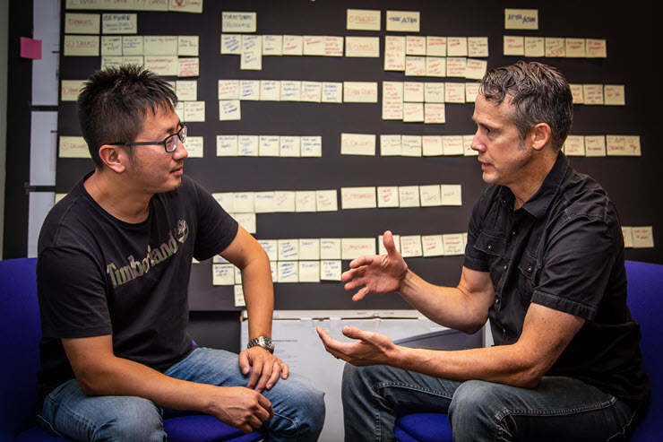 Marcus Wheeler and Bill Zhong sit facing each other in front of a black poster board covered in yellow sticky notes.
