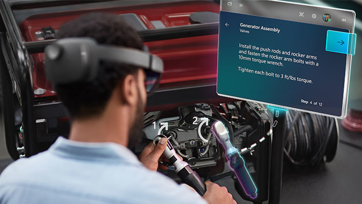 A mechanic wearing a HoloLens 2 headset reads instructions off a hologram while repairing a generator