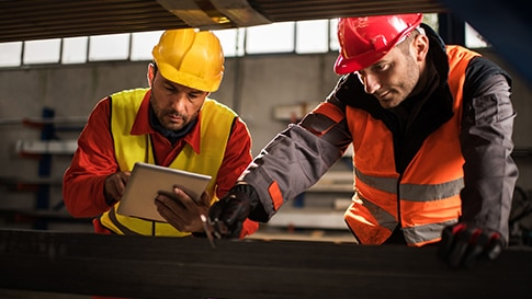 Manufacturing worker uses tablet while colleague looks at equipment