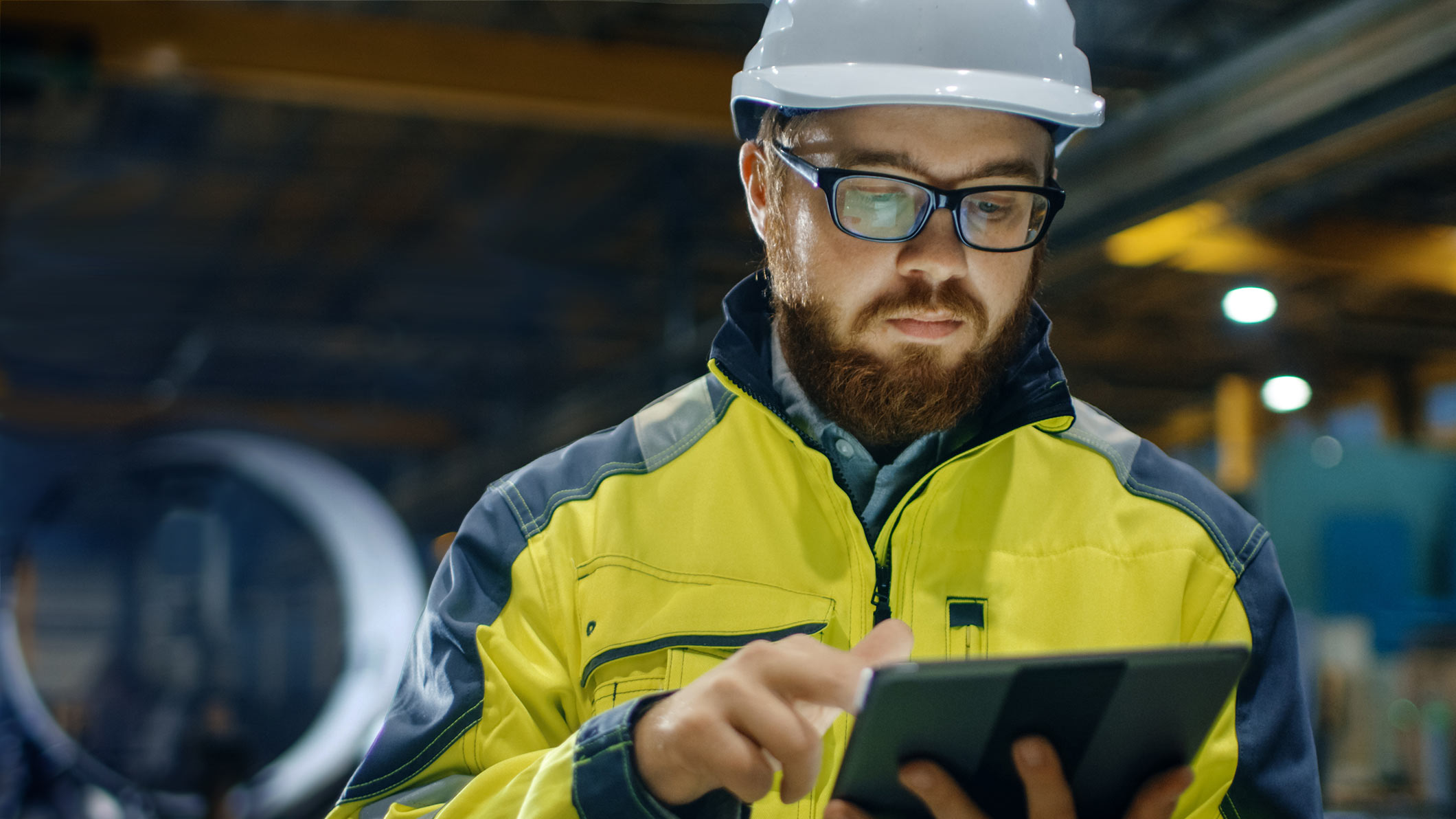 manufacturing worker looking at tablet in factory setting