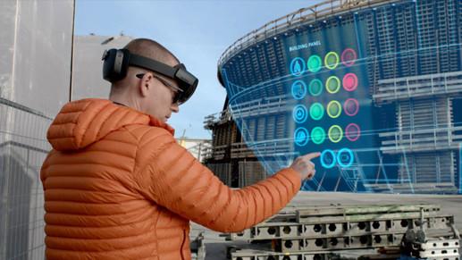 Homme équipé d'un casque HoloLens2, debout sur un site de construction, étudiant l'hologramme de données d'un bâtiment