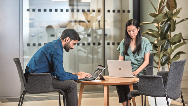 Man and woman sitting at a table. The man interacting with a Surface Pro. The woman is working on a laptop.